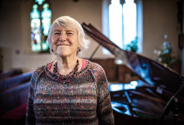 Woman standing in front of a piano and smiling