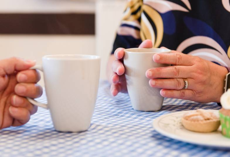 Close up of the hands of two people holding cups of tea