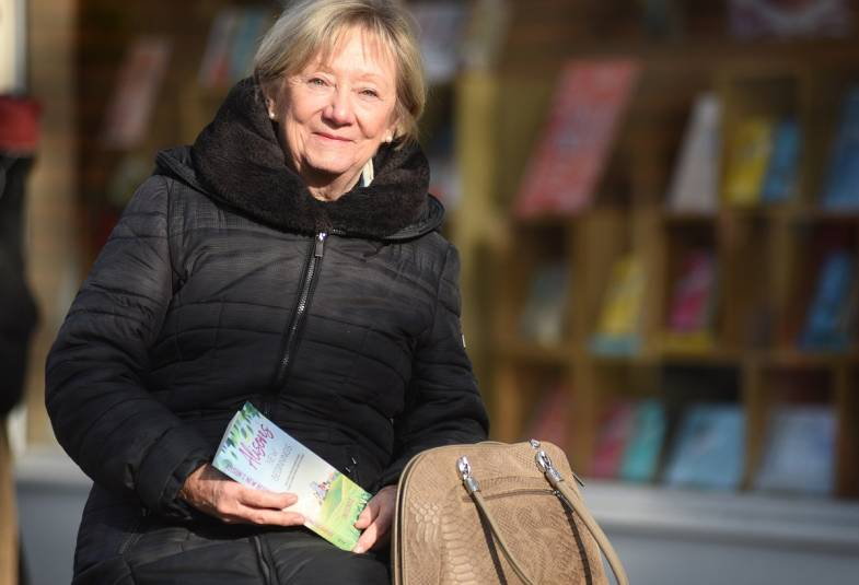 Woman sitting on a bench outside a bookstore holding her book