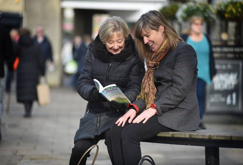 Two women sitting outside reading a book