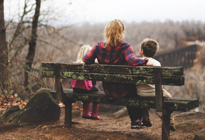 Women on wooden bench with her arms around a child wither side of her
