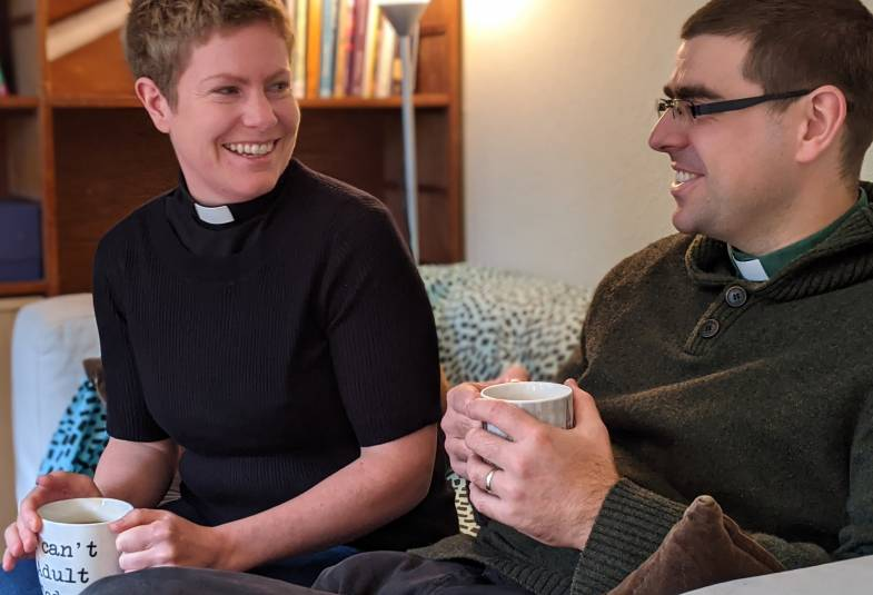Two priests drink two while smiling at one another