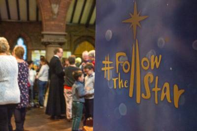 A #FollowTheStar banner in focus with a church congregation in the background, out of focus.