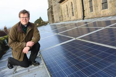 Vicar Will Hughes poses on the roof of a church with solar panels