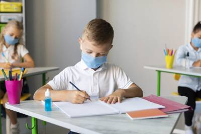 Children distanced in classroom wearing masks covid