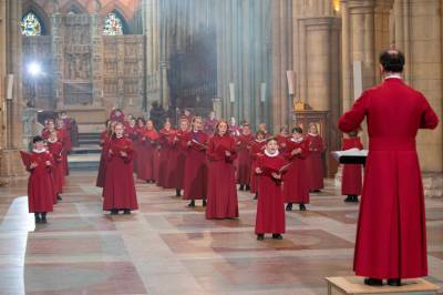 Truro Cathedral choristers are shown in red singing the Gee Seven song