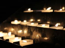 Rows of tealight candles in the darkness