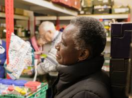 Profile of woman in a food bank, volunteers working in the background