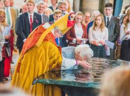 Bishop in cathedral baptises older lady in font