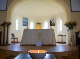 Candle lit in a bowl in front of church altar