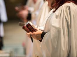Profile of female clergy member holding bible