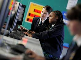 two secondary school children sitting at a computer