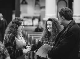 Three young people smiling and chatting inside church
