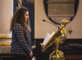 Young woman talking at cathedral lectern