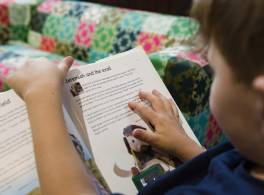 over the shoulder shot of child reading book