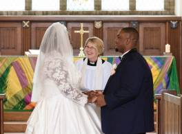 Bride and groom face each other at front of church, vicar smiling