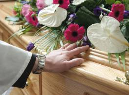 Clergy lays hand on coffin at funeral