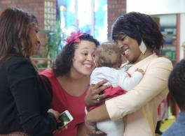 Women smiling at baby at baptism