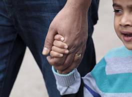 Adult hand holding child's hand