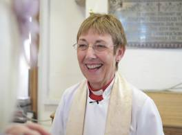 Smiling female vicar in robes