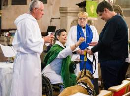 Clergy in wheelchair, administering communion to blind woman with guide dog