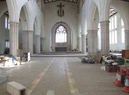 Interior of a church with construction materials and tools layout out in the aisles
