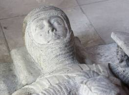 Close up of the head of a Medieval soldier's effigy made of white stone