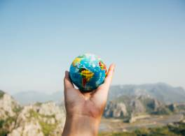 A hand holding a toy of planet Earth with rocky mountains in the background