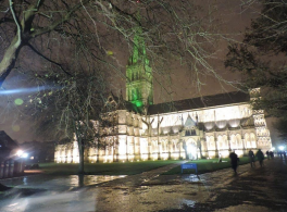 Salisbury Cathedral at night with its spire lit up in Green