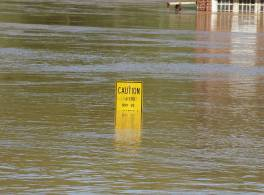 Water rising above a caution sign with a building in the background