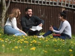 Young adults sat on grass laughing with bible