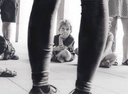 A boy sitting on the floor looking up at a group of adults in black and white.