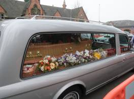 A coffin in a silver hearse with flowers laid around it