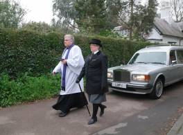 A male vicar and a female funeral director walk side by side in front a silver funeral car