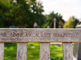 Focus on the words Loved and always remembered carved on a memorial bench