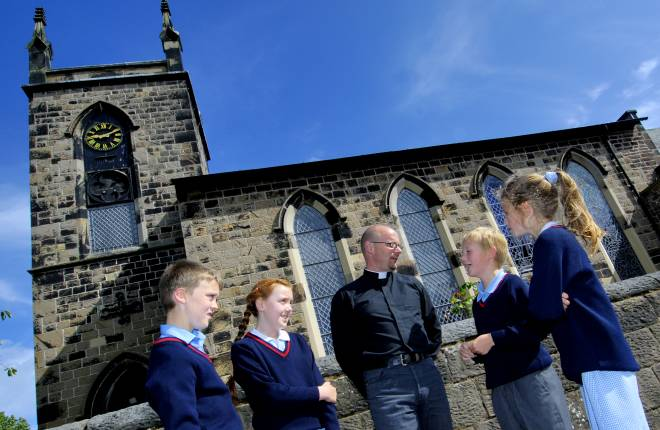 four school children in uniform stand outside church with member of clergy