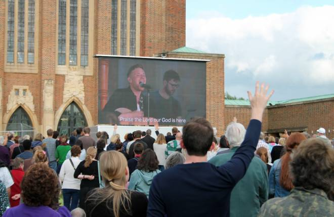 People taking part in service outside cathedral, watching singer on large screen
