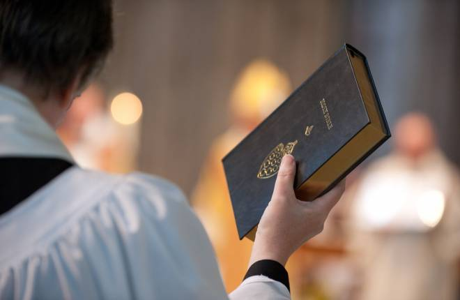 Member of clergy holding bible in the air