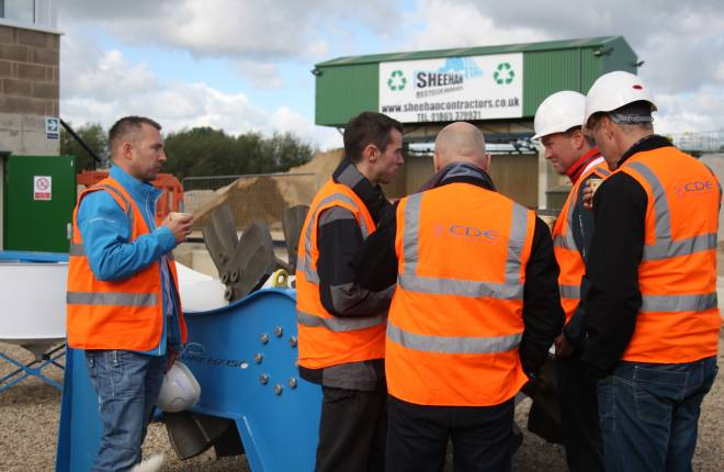 A group of builders wearing high visibility jackets talking at a recycling centre.
