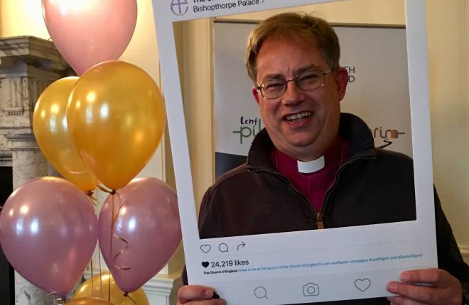 The Bishop of Oxford with an Instagram frame smiling at the camera