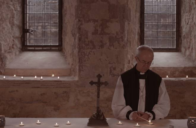 The Archbishop of Canterbury lighting a candle in the Crypt Chapel at Lambeth Palace.