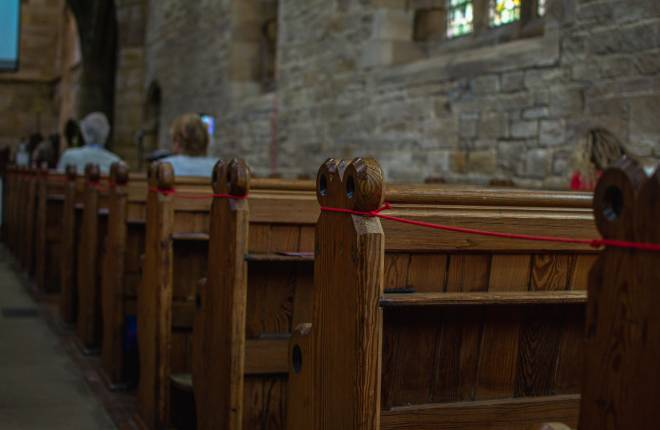 Pews within a church with people socially distant
