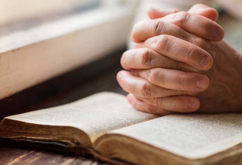 An open bible with hands clasped resting on it in prayer