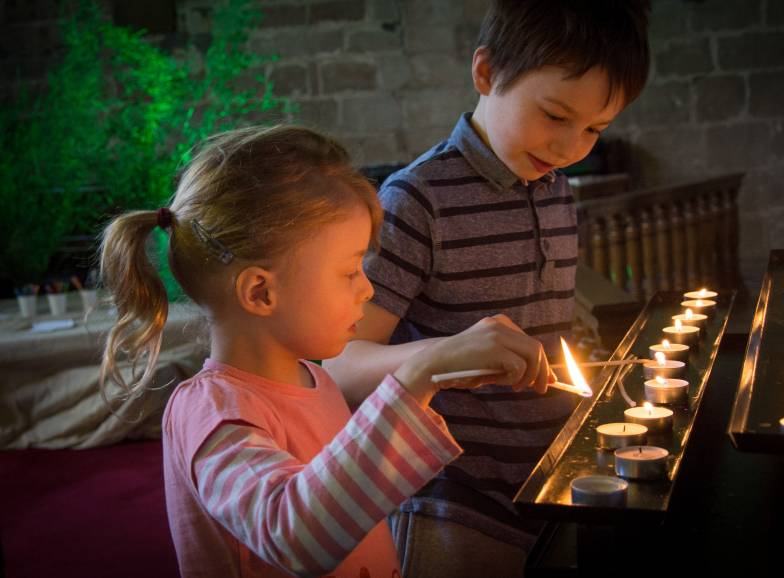 Two children lighting candles